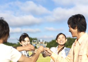 青空の下で白ワインを飲む若者たちの写真素材 [FYI03911501]
