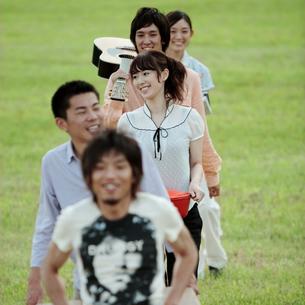草原でテーブルを運ぶ若者たちの写真素材 [FYI03911515]