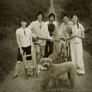 一本道に立つ若者たちと犬の写真素材 [FYI03911536]