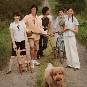 一本道に立つ若者たちと犬の写真素材 [FYI03911538]