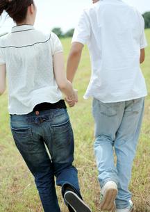草原で手をつなぎ走るカップルの写真素材 [FYI03911564]