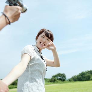 草原でビデオを撮り合うカップルの写真素材 [FYI03911595]