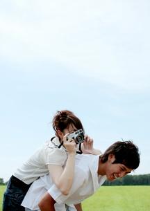 草原で写真を撮り合うカップルの写真素材 [FYI03911602]