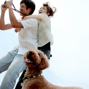じゃれながら写真を撮るカップルと犬の写真素材 [FYI03911612]
