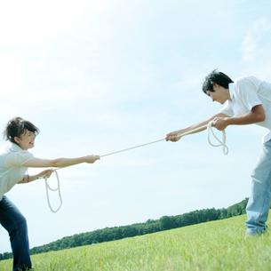 草原で綱引きをするカップルの写真素材 [FYI03911630]