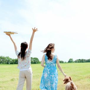 草原を歩く2人の女性と犬の写真素材 [FYI03911651]