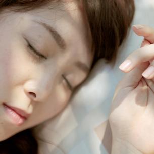 外で昼寝をする女性の写真素材 [FYI03911668]