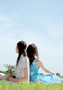 草原で背を合わせ座る2人の女性の写真素材 [FYI03911673]