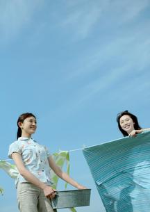 草原で洗濯物を干す2人の女性の写真素材 [FYI03911685]