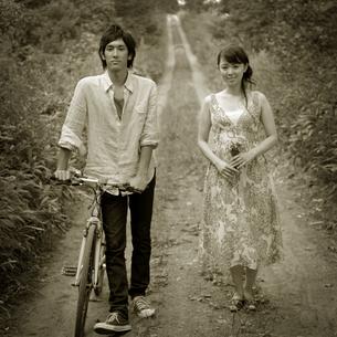 一本道に立つカップルの写真素材 [FYI03911724]