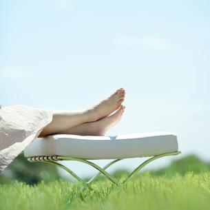 草原でくつろぐ女性の足元の写真素材 [FYI03911749]