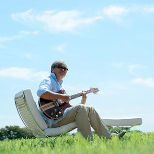 草原でギターを弾く中高年の男性の写真素材 [FYI03911753]