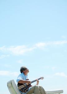 草原でギターを弾く中高年の男性の写真素材 [FYI03911754]