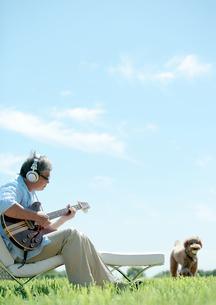 草原でギターを弾く中高年の男性の写真素材 [FYI03911759]