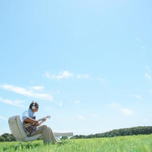 草原でギターを弾く中高年の男性の写真素材 [FYI03911761]