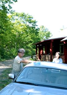 車を洗うシニア夫婦とログハウスの写真素材 [FYI03911770]