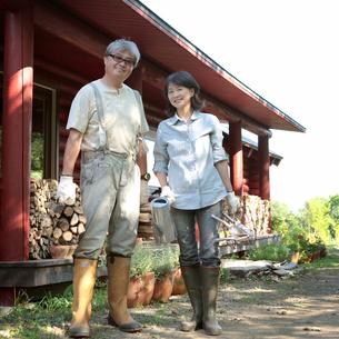 ログハウスの前のシニア夫婦の写真素材 [FYI03911782]