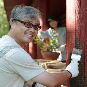 ログハウスのペンキを塗る中高年男性の写真素材 [FYI03911785]