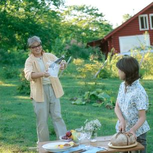 外で食事の準備をするシニア夫婦の写真素材 [FYI03911797]