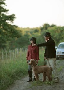 田舎道を散歩するシニア夫婦と犬の写真素材 [FYI03911823]