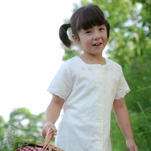 野花の入ったかごを持つ女の子の写真素材 [FYI03911839]