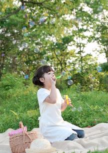 シャボン玉で遊ぶ女の子の写真素材 [FYI03911873]