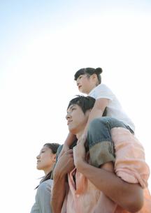 父親に肩車をしてもらう女の子と母親の写真素材 [FYI03911897]