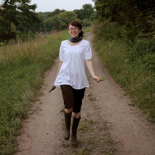田舎道を歩く女性の写真素材 [FYI03911912]