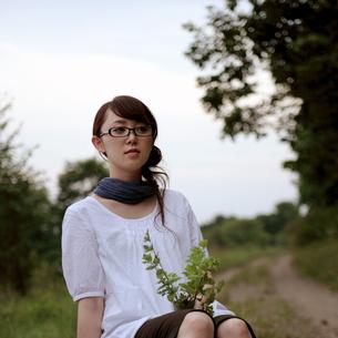 ミントを持って座る女性の写真素材 [FYI03911916]