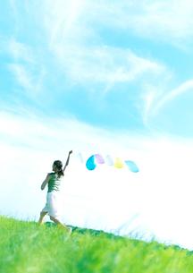 風船を持って草原を駆ける女性の写真素材 [FYI03912046]