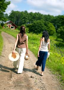 一本道を散歩する2人の女性の写真素材 [FYI03912076]