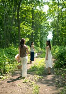 一本道を散歩する3人の女性の写真素材 [FYI03912099]