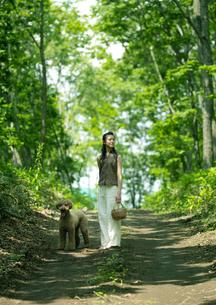 一本道に佇む犬と女性の写真素材 [FYI03912117]