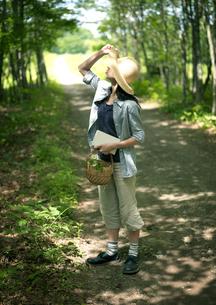 一本道を散歩する女性の写真素材 [FYI03912290]