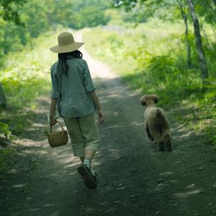 一本道を散歩する女性と犬の写真素材 [FYI03912294]