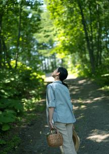 一本道で空を見上げる女性の写真素材 [FYI03912303]