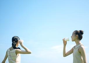 糸電話をする2人の女性の写真素材 [FYI03912338]