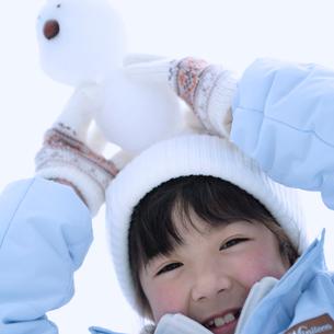 雪だるまを頭の上に乗せる女の子の写真素材 [FYI03912403]