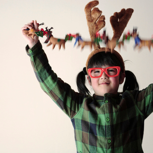 クリスマスグッズで遊ぶ女の子の写真素材 [FYI03912430]