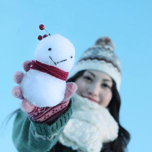 雪ダルマを持って微笑む女性の写真素材 [FYI03912542]