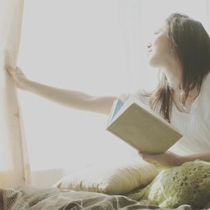 カーテンを開け窓の外を見る女性の写真素材 [FYI03912626]