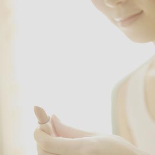 口紅を持つ女性の写真素材 [FYI03912695]