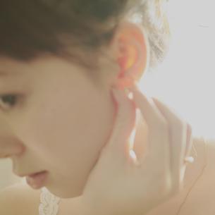 耳にピアスを合わせる女性の写真素材 [FYI03912712]