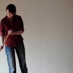 ほうきで床を掃く女性の写真素材 [FYI03912758]