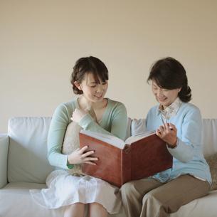 一緒にアルバムを眺める母娘の写真素材 [FYI03912782]