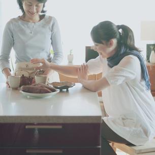 焼き芋に手を伸ばす娘と母の写真素材 [FYI03912796]