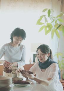 焼き芋を食べる娘とお茶を入れる母の写真素材 [FYI03912797]