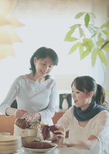 焼き芋を食べる娘とお茶を入れる母の写真素材 [FYI03912798]