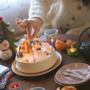 クリスマスケーキのキャンドルに火を灯す女性の写真素材 [FYI03912969]