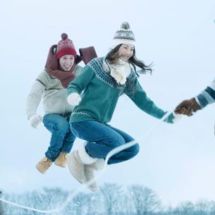 雪原で縄跳びをする若者たちの写真素材 [FYI03913224]